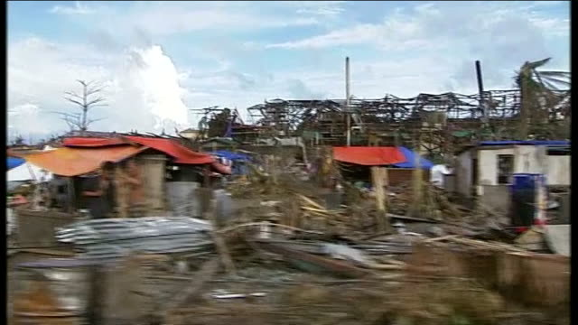vídeos de stock e filmes b-roll de day 6 int car s point of view along road with power cable fallen above road tracking shot past destroyed houses without roofs and debris covering... - cama de rede
