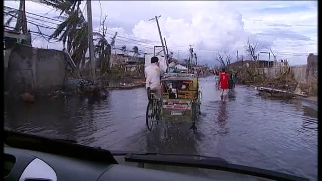 typhoon haiyan aftermath: day 6; leyte: int car driver's point of view following rickshaw and people walking along road as rain falls - フィリピン点の映像素材/bロール