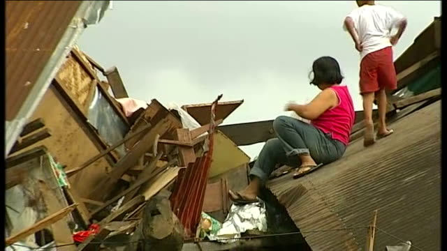typhoon haiyan aftermath: day 7; aid workers handing out rice bags and water bottles back view boy climbing up debris with rice and handing to woman... - フィリピン点の映像素材/bロール