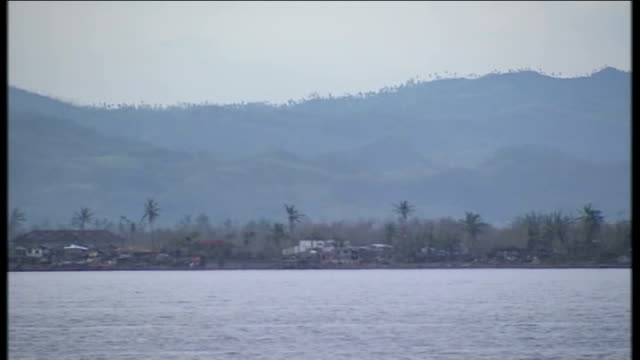 Family reconnected to relatives in London PHILIPPINES Tacloban Leyte Palm trees and damaged buildings on land seen from water