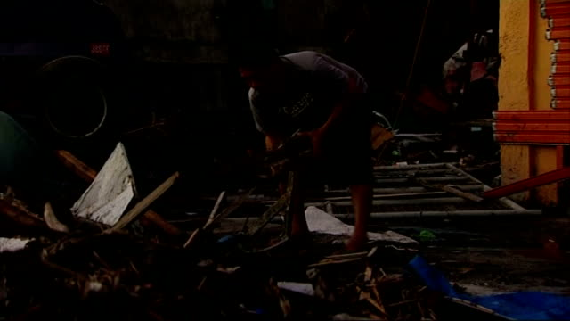 Situation in Tacloban PHILIPPINES Tacloban Silhouette of area devasted by Typhoon Haiyan PAN Man scavenging amongst debris Man covering his face...