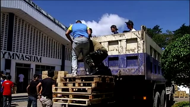 Aid supplies slowly starting to get through Cebu INT Sacks of food aid carried along inside warehouse Aid supplies being loaded onto lorry Truck...