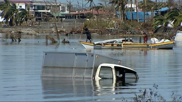 Fishing village of San Jose decimated PHILIPPINES Near Tacloban San Jose EXT Truck standing semi submerged in the coastal water after being swept out...