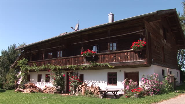 ms typical ancient bavarian farmer house with flowers with wooden first floor / massing, bavaria, germany - tradition stock-videos und b-roll-filmmaterial