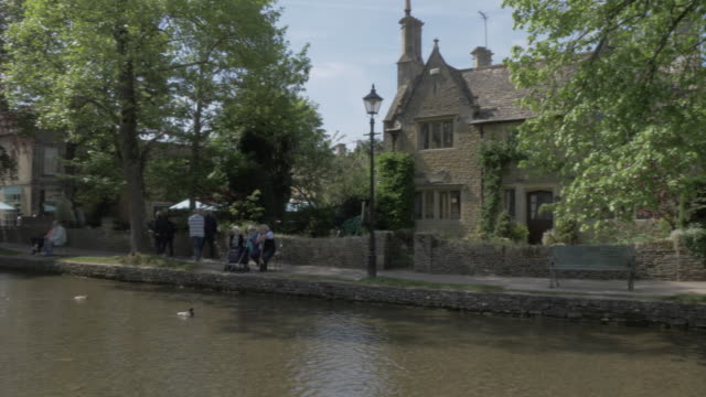 typical architecture on high street and river windrush in bourton on the water, cotswolds, gloucestershire, england, united kingdom, europe - windrush river stock videos and b-roll footage