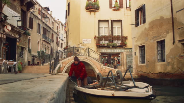 ms - typical back street and canal of venice, near campo san giacomo, boat docking and unloading merchandises - 1 minute or greater stock videos & royalty-free footage