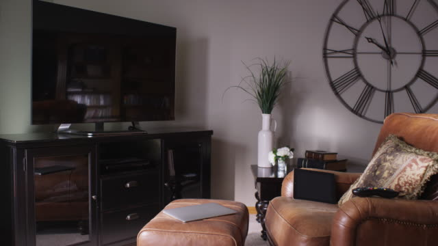 typical empty tv recreation family room featuring a wall clock, large screen tv, leather chair and laptop computer on a footstool. - armchair stock videos & royalty-free footage