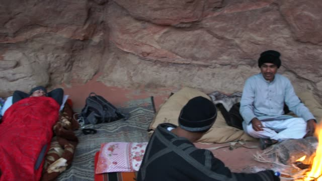 a typical morning at a wild camp in wadi rum desert with bedouins preparing breakfast around the campfire - eco tourism video stock e b–roll