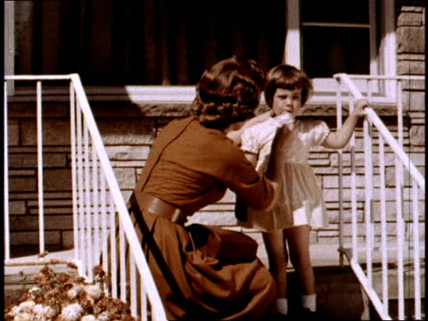 / typical suburban American housewife loading her kids into the Rambler station wagon / mother stops to wipe little girl's nose before getting into...