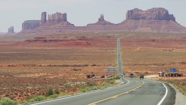 typische ansicht des monument valley und highway 163 - tafelberg felsformation stock-videos und b-roll-filmmaterial