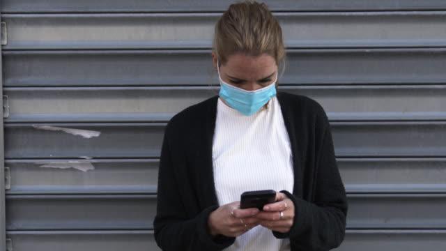 vídeos de stock e filmes b-roll de typing a message during the pandemic - máscara cirúrgica