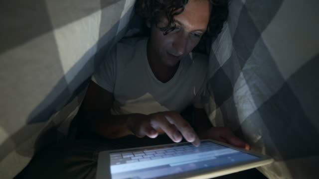 Typing a message under the blanket.