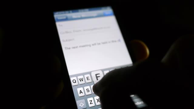 digitare un messaggio di testo al buio - dito umano video stock e b–roll