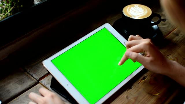 Typen op de tablet bij koffiehuis, met groen scherm