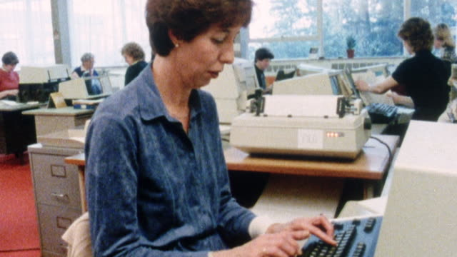 vídeos de stock e filmes b-roll de montage typist working at a computer in an office and a printer producing a document / united kingdom - 1980