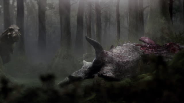 A Tyrannosaurus Rex in a forest feeds on a carcass in a computer-generated animation.
