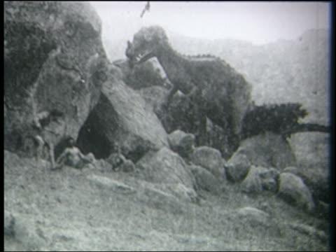 b/w 1915 tyrannosaurus rex stands over cavemen by rocks - tyrannosaurus rex stock videos and b-roll footage