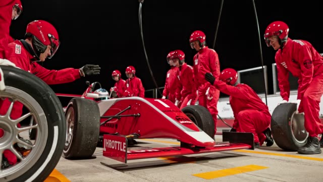Tyres being changed on the red formula in the pit stop at a night race