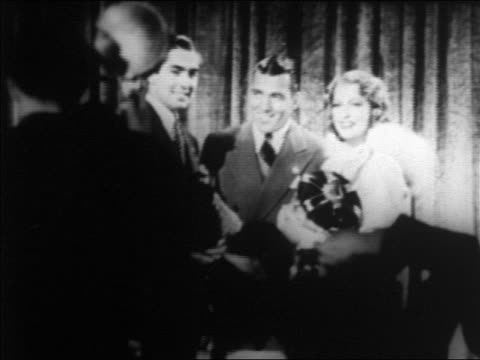 tyrone power ed sullivan jeanette macdonald posing for photographers indoors / newsreel - female with group of males stock videos and b-roll footage