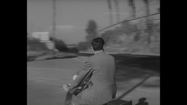 Tyrone Power rides down street towards camera / convertible drives along in front of him with cameraman shooting film of him / Power passes through...