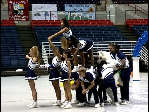 uconn cheerleaders and mascot doing a cheer - チアリーダー点の映像素材/bロール