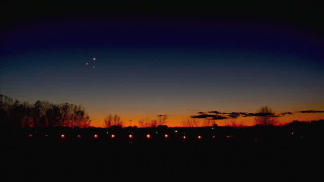 vídeos de stock, filmes e b-roll de ws ls ufos flying over horizon at sunset, neenah, wisconsin, usa - ufo