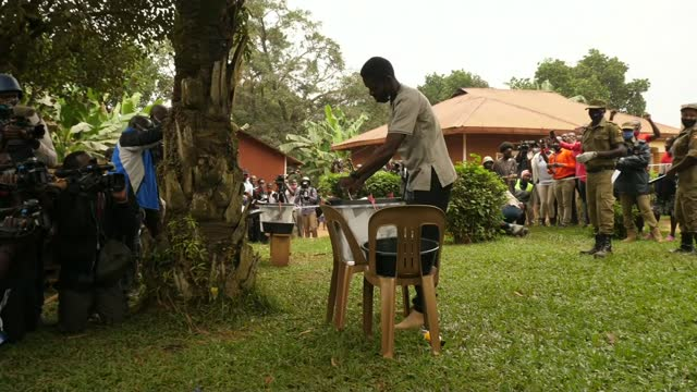 ugandan general election: counting of votes begins; uganda: kampala: ext gv ballot counter holding ballot up for crowd to see gv crowd behind tape... - politics stock videos & royalty-free footage
