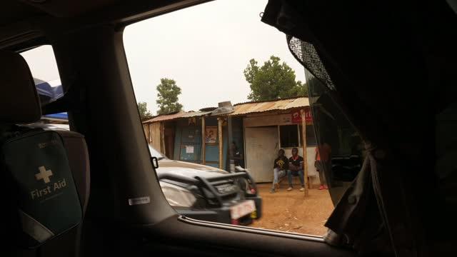 ugandan general election: museveni wins amid violence and allegations of fraud; uganda: kampala: ext / night reporter to camera day gv car along road... - kampala stock-videos und b-roll-filmmaterial