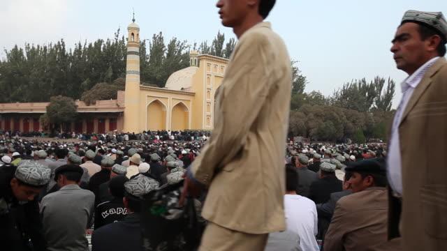 uighur muslims gather at id kah mosque for prayer - 新疆ウイグル自治区点の映像素材/bロール