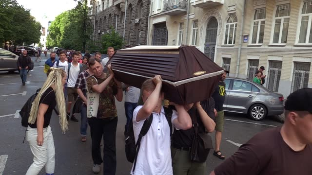Ukrainian activists carry a coffin during a symbolic funeral of the Ukrainian Constitution to the Presidential office in Kiev Ukraine 27 June 2019...
