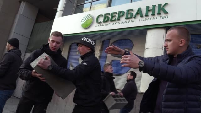 vidéos et rushes de ukrainian activists of national corps burn torchesmake graffitiand build a wall which block entrance to the sberbank of russiaduring a protest in... - parpaing