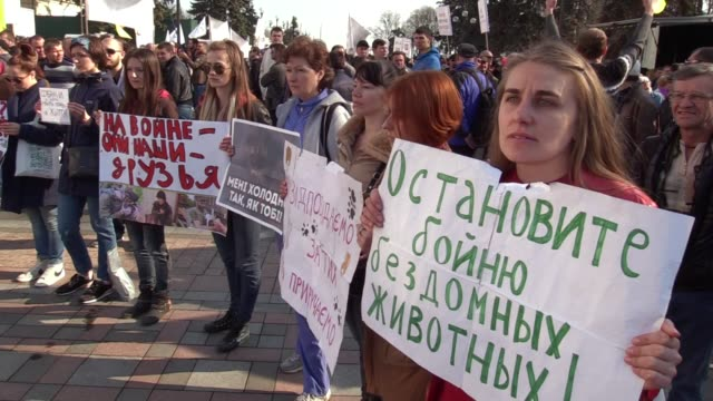 Ukrainian animal rights activists hold placards and shout slogans ' Ukraine without dog hunters' and otherduring a rally with their dogs near the...