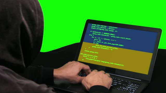 ukrainische hacker typing code hacking auf seinem laptop mit ukrainischer flagge auf dem grünen bildschirm hintergrund hacker typisierung code hacking auf seinem laptop mit kanada-flagge auf ihm greenscreen hintergrund - schwarzes hemd stock-videos und b-roll-filmmaterial