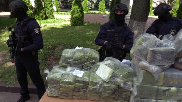 Ukrainian police officers stand guard in front of bags of cocaine seized during a special operation during a pess conference of the leadership of the...