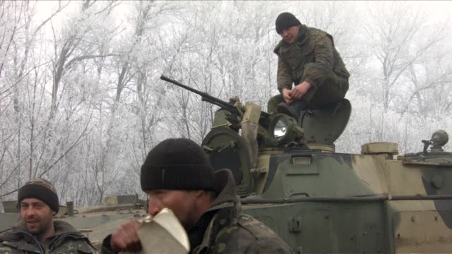 stockvideo's en b-roll-footage met ukrainian soldiers near the frontline with prorussian rebels play football on the road as a fragile ceasefire comes into force in ukraine - staakt het vuren