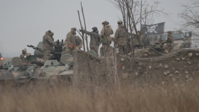 "ukrainian soldiers of volunteer battalion ""azov"" on military armored vehicles at the frontline against russia-backed rebels. - ウクライナ点の映像素材/bロール"