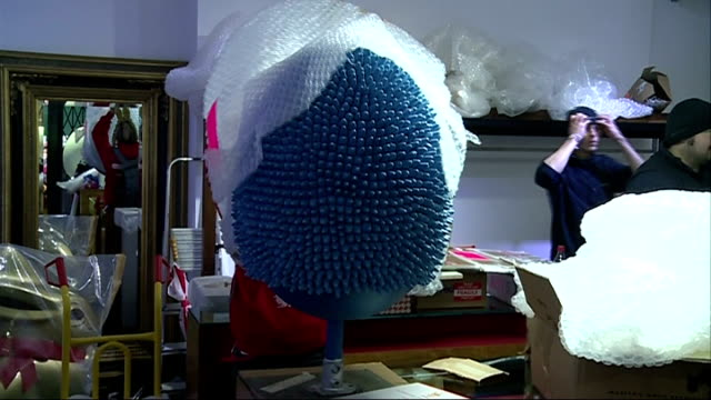 Uk's biggest Easter Egg Hunt ENGLAND London INT Bubble wrap being removed from decorated giant egg Close shot egg Bubble wrap being removed from blue...