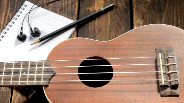 vídeos y material grabado en eventos de stock de ukulele de guitarra cuaderno y un lápiz en madera - estilo de música