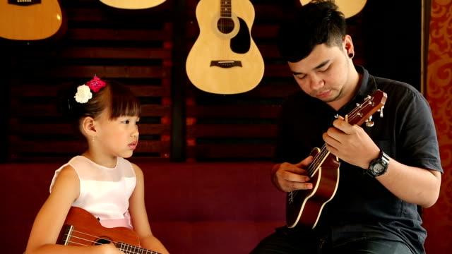 vídeos de stock, filmes e b-roll de ukulele guitarra professor ensinar música - ukulele