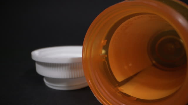 ultra close-up macro moving slider shot of empty prescription bottle on a black studio background with copy space - pill bottle stock videos & royalty-free footage
