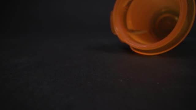 コピースペースを持つ黒いスタジオの背景に空のローリング処方箋ボトルの超クローズアップマクロ移動スライダーショット - 注意欠陥過活動性障害点の映像素材/bロール