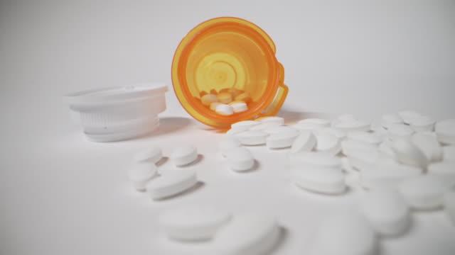 オレンジ色の処方箋ボトルの超クローズアップマクロ移動スライダーショットは、店頭でこぼれ落ちる, アレルギー, 麻薬, 鎮痛剤薬は、白いスタジオの背景に投げ出さ - 注意欠陥過活動性障害点の映像素材/bロール
