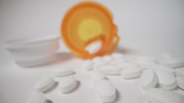 カウンターの上にこぼれるオレンジ色の処方箋ボトルの超クローズアップマクロ移動スライダーショット, アレルギー, 麻薬, 鎮痛剤薬の丸薬は、白いスタジオの背景に捨てられました - 注意欠陥過活動性障害点の映像素材/bロール