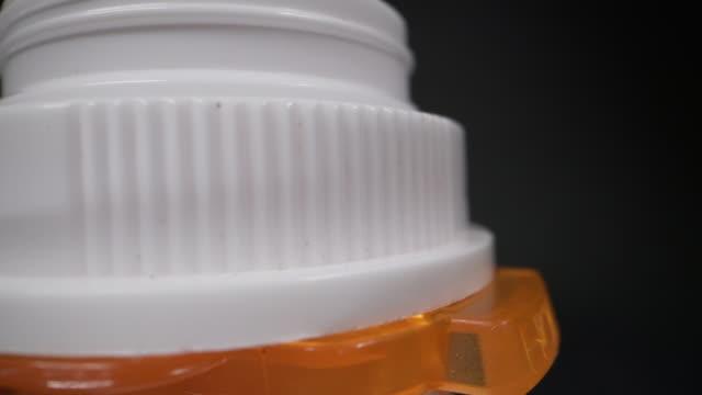 黒い背景に対するオレンジ色の処方薬ボトルの上部の超クローズアップマクロ回転ショット - 注意欠陥過活動性障害点の映像素材/bロール