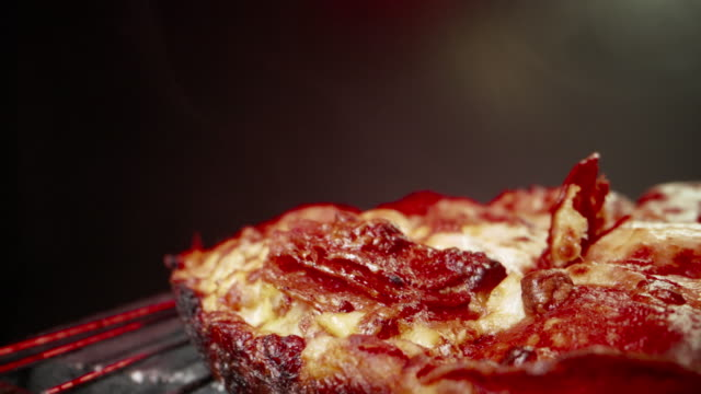 ultra close-up wide angle macro shot flying through delicious steaming hot deep dish pepperoni pizza fresh out of the oven on a cooling rack under a heat lamp with a dolly camera shot rolling backwards and ending with copy space - pizza stock videos & royalty-free footage