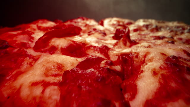 ultra close-up wide angle macro shot of delicious steaming hot deep dish pepperoni pizza fresh out of the oven on a cooling rack under a heat lamp with a dolly camera shot rolling backwards and ending with copy space - microwave meal stock videos & royalty-free footage