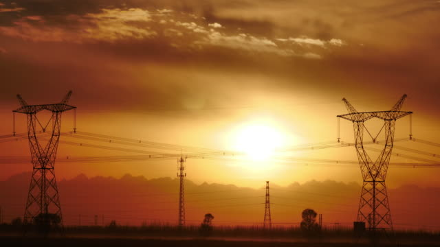 t/l  ultra high voltage transmission tower in sunset - electricity pylon stock videos & royalty-free footage