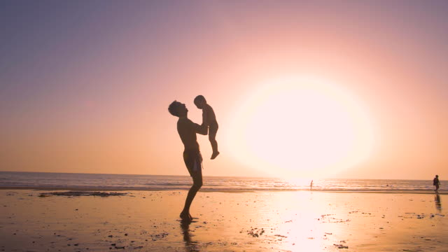 vídeos de stock, filmes e b-roll de ultra slow motion - silhouette of father and son playing together in the beach at sunset - balançando