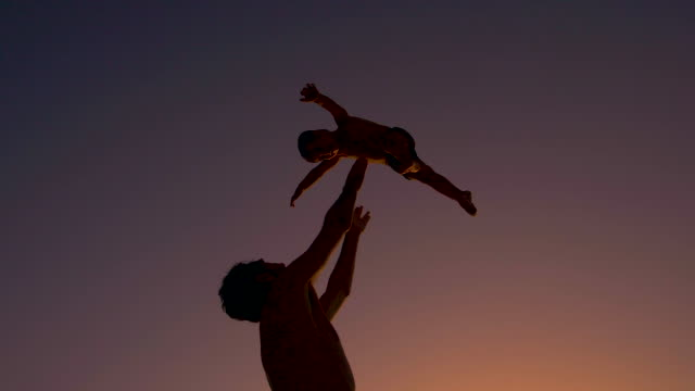 ultra slow motion - silhouette of father and son playing together in the beach at sunset - silhouette stock videos & royalty-free footage