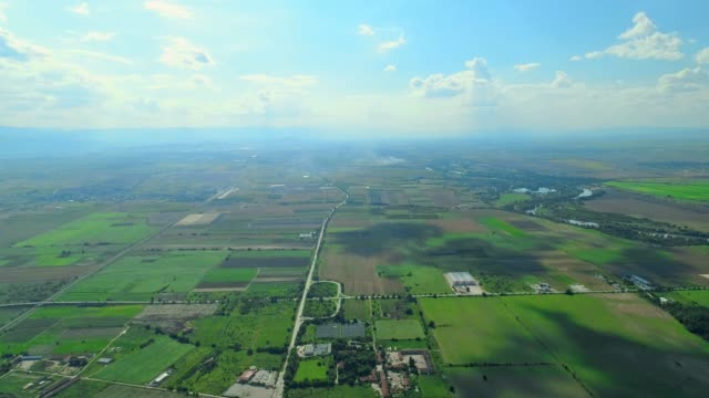 Ultra wide aerial stationary view over highway and agriculture fields